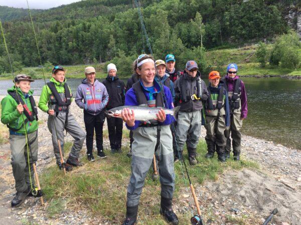 8 ungdommer på en elvebredd med fiskeutstyr. En gutt står foran med en fisk i hendene som smiler.