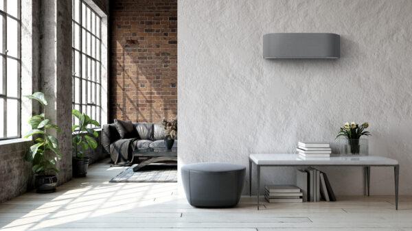 Grå varmepumpe på betongvegg med et lite bord og en puff under.